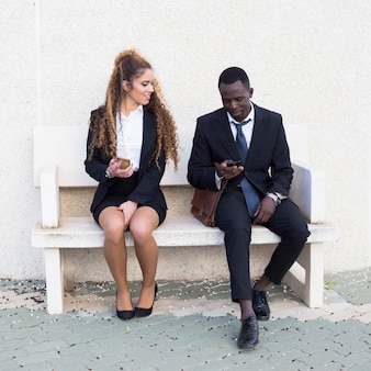 Paare von den geschäftsleuten, die smartphone auf bank betrachten