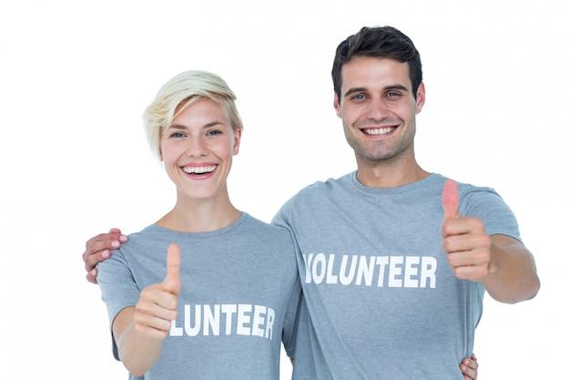 Paare von den jungen freiwilligen, die oben daumen gestikulieren