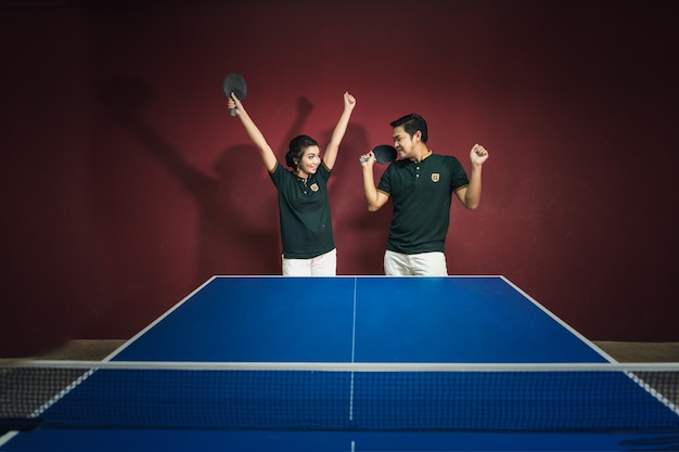 Paare von den jungen leuten, die pingpong mit den pingpongpaddeln spielen, die spaß haben
