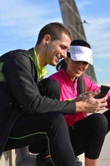 Paare von den läufern, die eine anwendung von leichtathletik während rest des laufs schauen