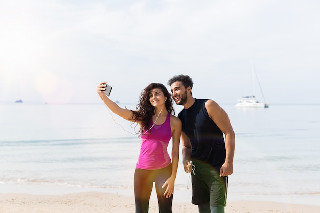 Paare von den läufern, die selfie-foto beim auf strand zusammen rütteln machen