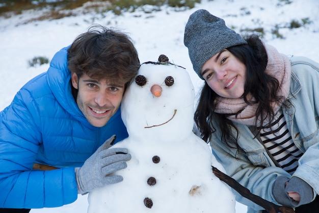Paare von den liebhabern, die im schnee mit einem schneemann genießen.
