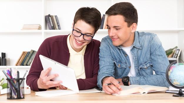 Paare von den mitschülern, die tablette betrachten