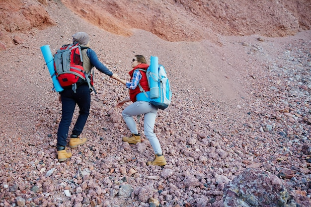 Paare von den reisenden, die berg klettern