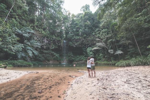 Paare von den touristen, die natürliches pool und wasserfall im regenwald von lambir hills national park, borneo, malaysia betrachten