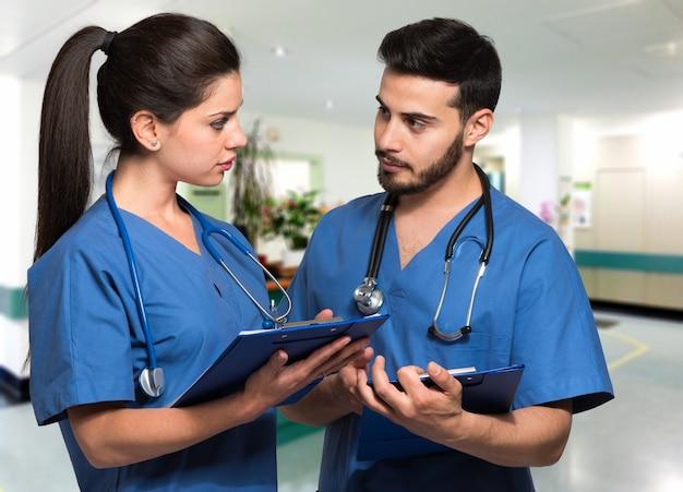 Paare von doktoren, die in einer krankenhaushalle sich besprechen