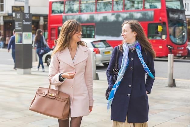 Paare von frauen, die london-straßen entlang gehen