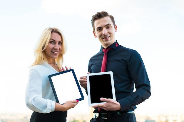 Paare von geschäftsmännern, von schönem brunettemann und von attraktiven blondinen stehen auf dem dach und schauen in den tabletten