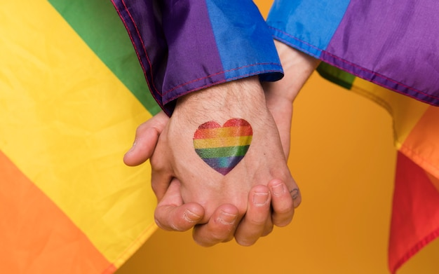 Paare von händen von homosexuellen männern mit regenbogenherzbild