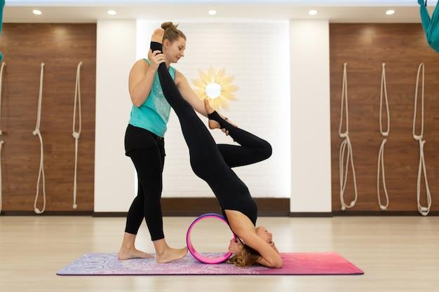 Paare von jungen frauen in einem sportkleidungsyoga drehen herein die turnhalle mit einem yoga