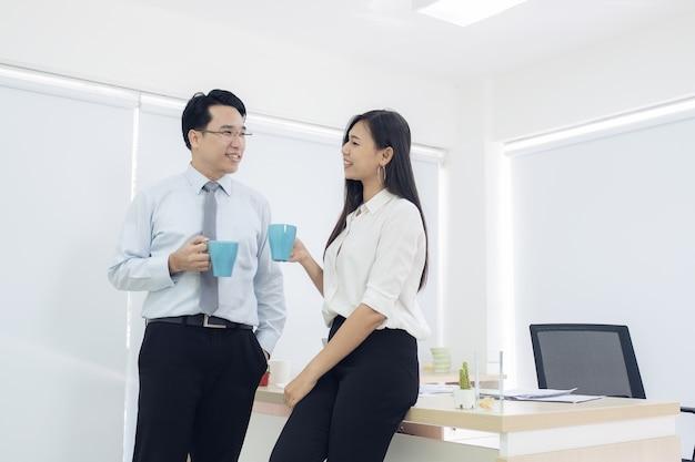 Paare von jungen kollegen in der formellen kleidung, die am arbeitsplatzbüro steht