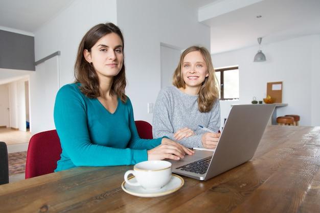 Paare von studenten, die zu hause am projekt zusammenarbeiten