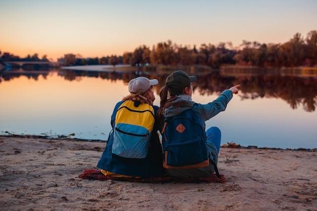 Paare von touristen mit den rucksäcken, die durch herbstflussbank sich entspannen
