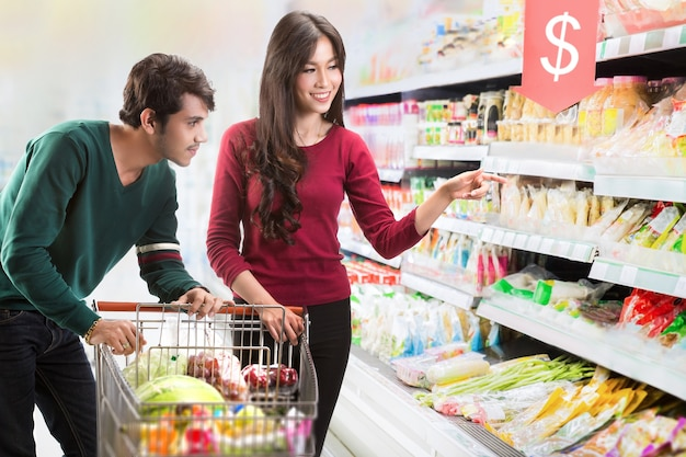 Paare wählen lebensmittel im supermarkt