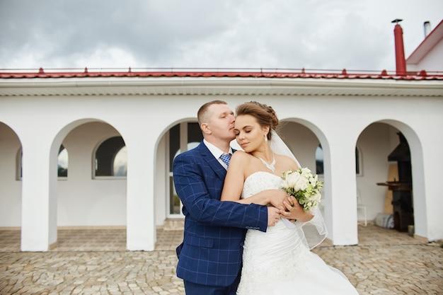 Paare wed umarmung und küssen folgende häuser nahe wasser