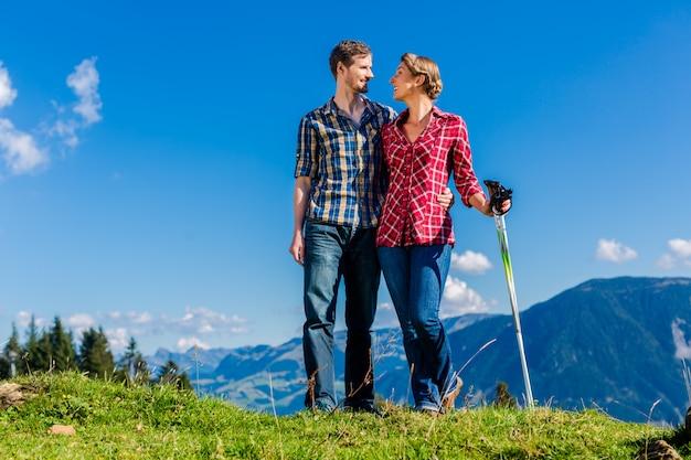 Paare, welche die ansicht genießen, die in den alpinen bergen wandert