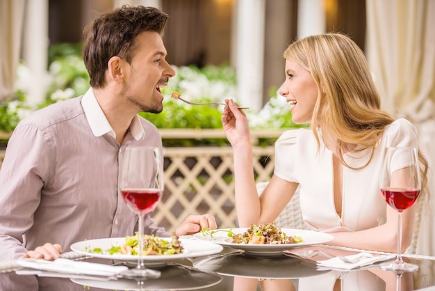 Paare, welche die mahlzeit im restaurant genießen und wein trinken.