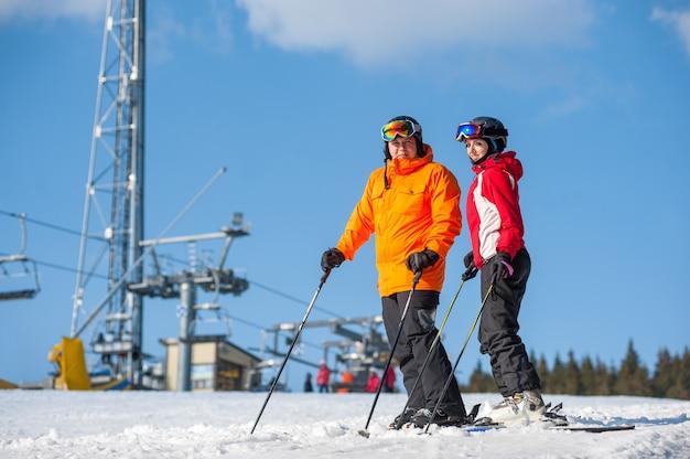 Paare, welche die skis stehen auf gebirgsoberseite zusammen halten