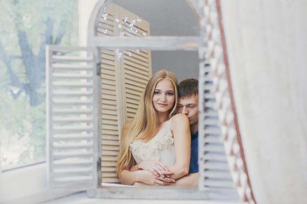 Paare zu hause, die im spiegel nahe dem fenster schauen.