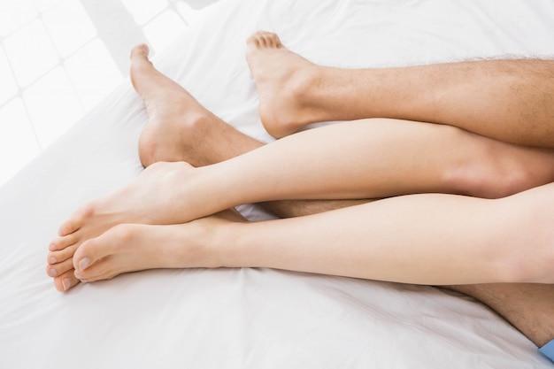 Paarfüße, die auf bett im schlafzimmer kuscheln