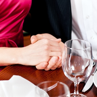 Paarhändchenhalten auf einer restauranttabelle
