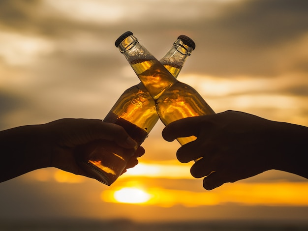 Paarhände, die bierflaschen halten und auf dem sonnenuntergangstrand schlagen