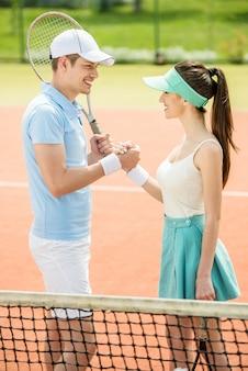 Paarhändeschütteln am tennisplatz nach einem match.