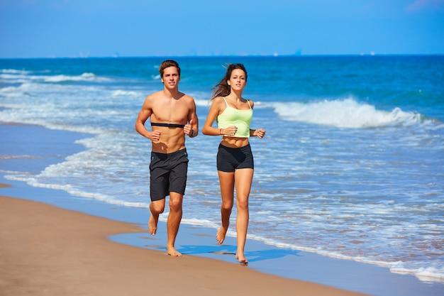 Paarjunge, der in den strand am sommer läuft