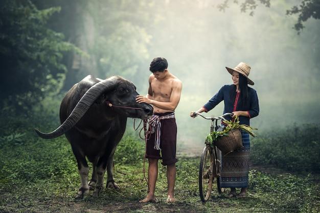 Paarlandwirt im landwirtsanzug mit büffel