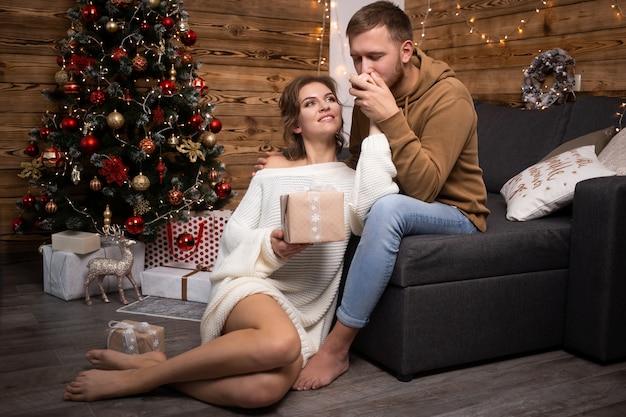 Paarleute feiern weihnachten nahe schön verziertem weihnachtsbaum