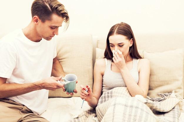 Paarpflege kranke frau, die sich die nase putzt, nimmt eine tasse mit heißem getränk im schlafzimmer