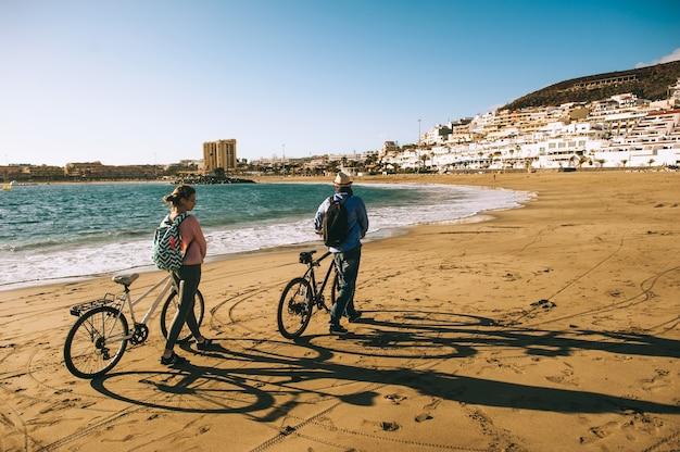 Paartouristen mit dem fahrrad-aufpassendem sonnenuntergang.