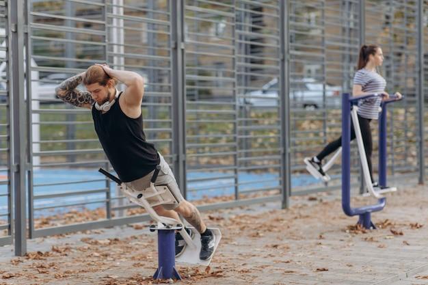 Paarübung im park. training für perfekte hüften. athletische junge frauen und mann in der sportkleidung, die draußen körperliche übungen mit trainer im grünen park tut.