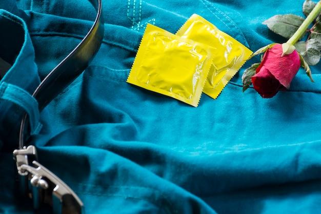 Pack kondome mit rosen auf hosen mit gürtel