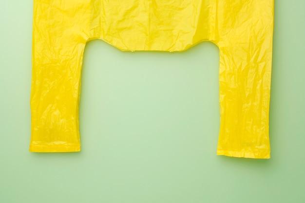Packen sie gelbe tasche auf grünem hintergrund. kein zellophan. platz für text kopieren.