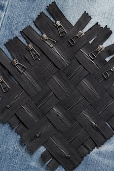 Packen sie viele schwarze metall-messing-reißverschlüsse mit schiebermuster für handgemachtes nähen, schneidern, lederarbeiten, auf dem blauen holzhintergrund ein