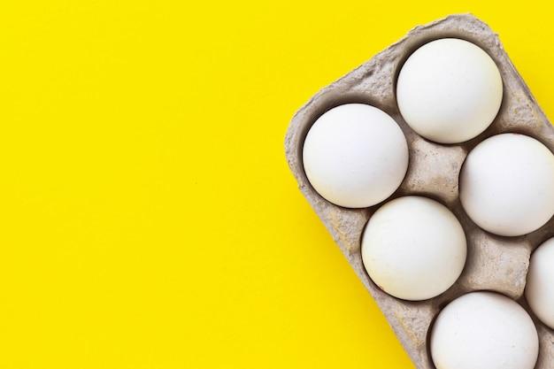 Packung der hühnereier der farm im pappbehälter auf gelbem hintergrund. gesundes essen. flache lage, draufsicht mit kopierraum.