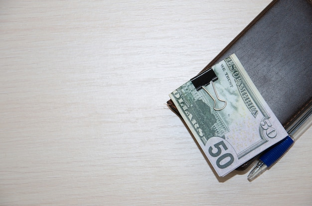 Packungen mit echten dollar-banknoten im notebook auf einem holztisch.
