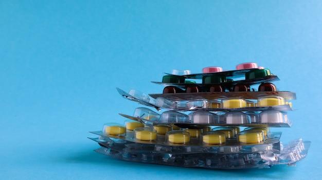 Packungen mit pillen in verschiedenen formen und farben sind auf blauem hintergrund gestapelt. kapseln sind in blisterpackungen verpackt. verschiedene medikamente. medikamentöse behandlung. gesundheitsfoto. platz kopieren.