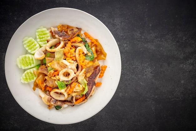 Pad see ew pla muek, thailändisches essen, gebratene sojasaucennudeln mit tintenfisch, ei, salat, karotte serviert mit gurke auf dunklem texturhintergrund, draufsicht