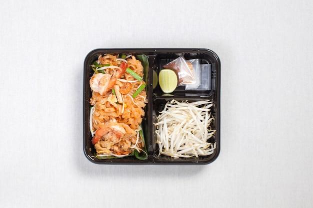 Pad thai goong sod mit sojasprossen in schwarzer plastikbox, auf eine weiße tischdecke, lebensmittelbox, thai-essen.