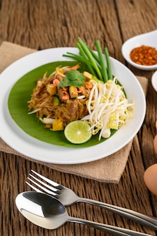 Pad thai in einem weißen teller mit zitrone, eiern und gewürzen auf einem holztisch.