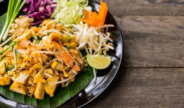 Pad thai in einer schwarzen schüssel mit eiern und gewürzten garnelen auf einem holztisch.
