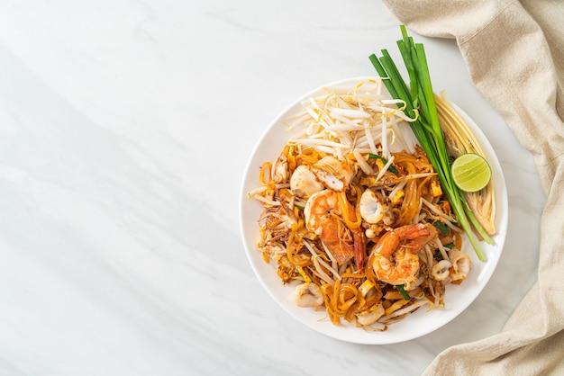 Pad thai seafood - gebratene nudeln mit garnelen, tintenfisch oder oktopus und tofu nach thailändischer art