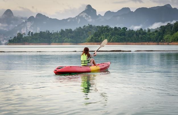 Paddel der jungen frau ein kajak auf der lagune, kayaking auf natürlichem reservoir