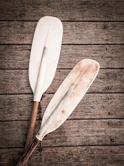 Paddel für kanu- oder kajakboot auf bretterboden. kajakboot für wassersportaktivitäten.