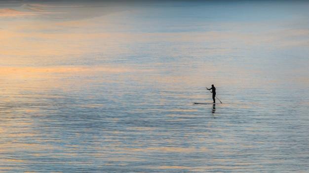 Paddelboarder im ozeanpaddeln während des sonnenuntergangs, der in christchurch, neuseeland, aufgenommen wurde