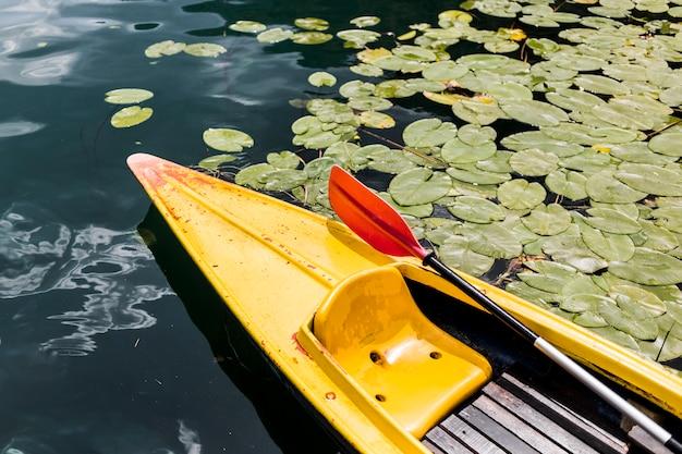 Paddelruder im gelben kanu, das auf see schwimmt