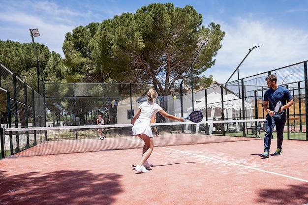 Padel-tennisspieler spielen an einem sonnigen tag auf einem außenplatz