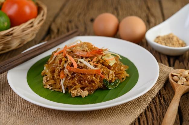 Padthai-garnelen in einer schwarzen schüssel mit eiern, frühlingszwiebeln und gewürzen auf holztisch.